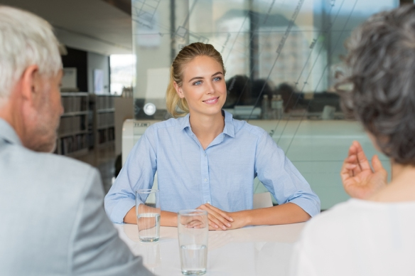 Portrait of woman sitting in front of manager and senior leader
